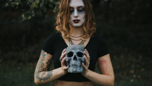 Girl with tattoos holding a gothic skull