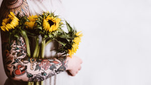 Woman with tattoos on her arm holding daffodils
