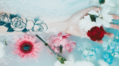 hand in the bath with rose tattoo on arm - pink & red flowers floating in the water