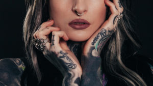 Woman with blonde hair & nose ring with tattoos hands & arms holding face - summer tattoo